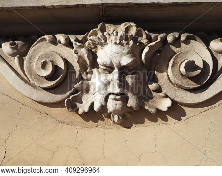 Detail Of A Relief On The Facade Of A Building. Stucco Molding In The Form Of A Man's Head With Curl