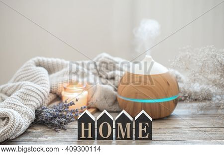 Aroma Still Life With A Modern Aroma Oil Diffuser On A Wooden Surface With A Knitted Element, Cozy D