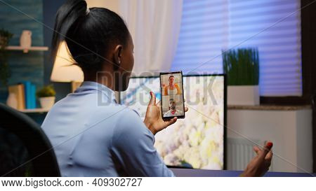 Black Young Lady Discussing On Webcam With Family Using Smartphone Taking A Break After Working Over