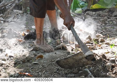 Workers' Feet And Hands Holding Hoe Stalks As Work Clearing Stones And Dirt In The Dusty Dirt Yard