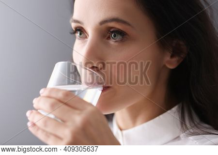Young Brunette Woman Drinking Water From Glass. Sufficient Fluid Intake Concept
