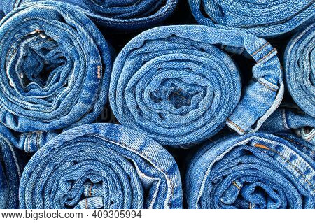 Denim Texture Background. A Group Of Blue Jeans Rolled Into A Tube Close-up, A Variety Of Comfortabl