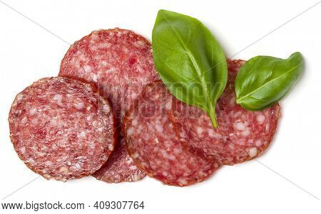 Slices of salami isolated over white background closeup. Sausage and basil leaves top view.