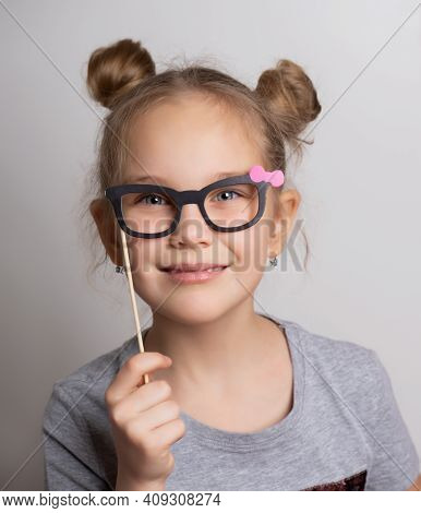 Cute Little Girl In A Carnival Mask With Paper Glasses. Festive Costume For A Masquerade. Attractive
