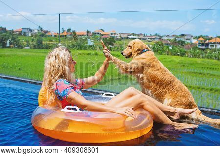 Funny Golden Labrador Retriever Give High Five To Happy Girl Swimming In Pool. Fun With Friends At P