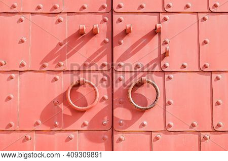 Metal gates, metal red door in medieval style, rings door handles and metal rivets. Metal architecture background, metal red gates,medieval gates