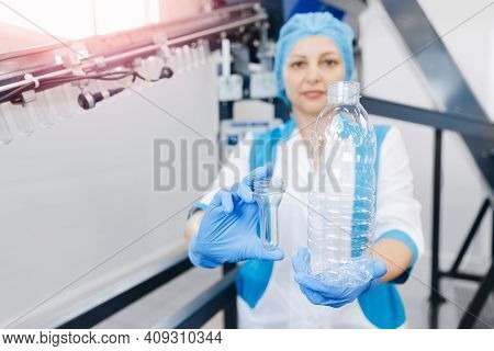 Woman Worker Holds Converting Plastic Preform Blank Into Pet Bottle For Drink Beverage Filling In Fo