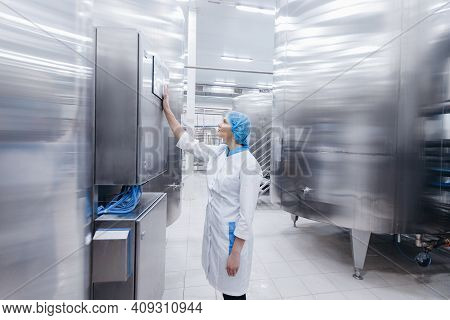 Worker Female Operator In Uniform Uses Process Control Panel Food Factory Production Line And Steel