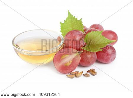 Organic Red Grapes, Seeds And Bowl Of Natural Essential Oil On White Background