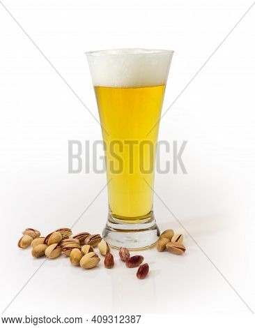 Lager Beer In A Beer Glass And Partly Peeled Roasted Salted Pistachio Nuts Beside On A White Surface