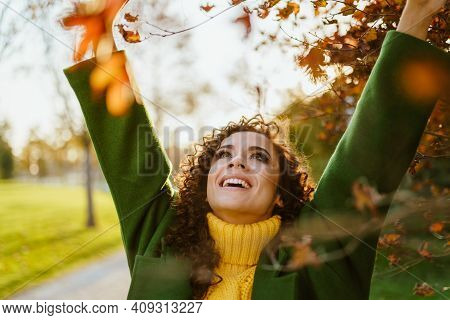 The Beauty Victoriously Threw Her Hands Up To The Sky And Smiles In The Autumn Park. High Quality Ph