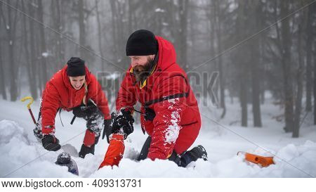 Mountain Rescue Service On Successful Operation Outdoors In Winter In Forest, Snow And Avalanche Con
