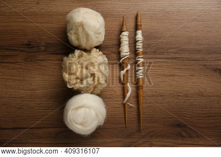 Soft White Wool And Spindles On Wooden Table, Flat Lay