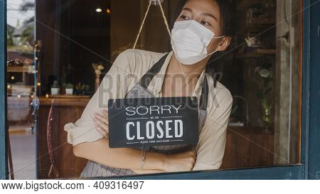 Young Asia Girl Wear Face Mask Turning A Sign From Open To Closed Sign On Glass Door Cafe After Coro