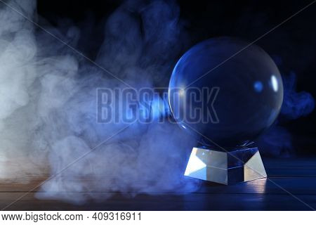 Magic Crystal Ball On Wooden Table And Smoke Against Dark Background, Space For Text. Making Predict