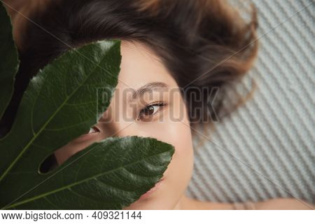 Concept Skincare Natural Flora Cosmetics. Beautiful Asian Woman With Smooth Skin In Tropical Leaves