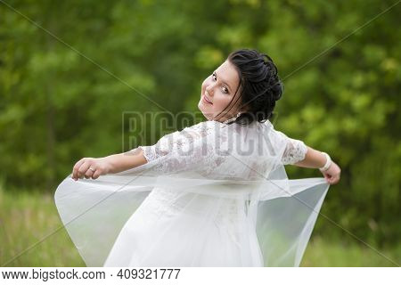 Portrait Of A Plump Bride With A Waving Veil Against A Background Of Summer Greenery.