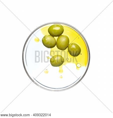 Green Olive And Oil On Petri Dish Over White Background
