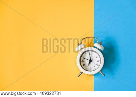 White Vintage Alarm Clock On Two Tone Color Grunge Paper , Yellow And Blue Background , Time Passing