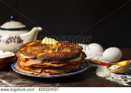 Pancake Day. The Tea-table With Pancakes. A Stack Of Pancakes On A Dark Wooden Table. Low Key, Horiz