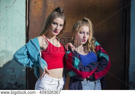 Two Funny Girls In Bright Clothes In The Style Of The Nineties Are Sitting Against The Background Of
