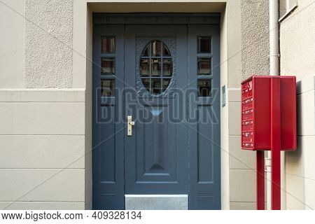 A View Of A Blue Front Door And A Red Mailbox In An Apartment Building.