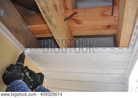 A Professional Is Installing Upvc Soffit, Nailing New Plastic Soffit To Wooden, Timber Rafters Of Th