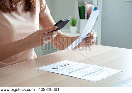 A Woman Uses A Smartphone To Scan The Barcode To Pay Monthly Phone Bills After Receiving An Invoice