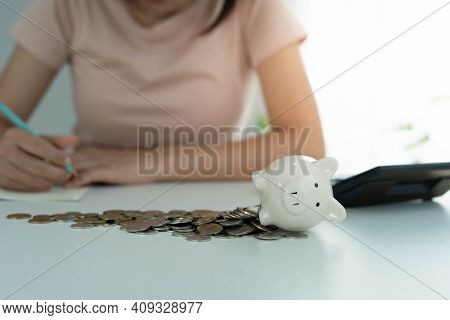Piggy Bank With A Pile Of Coins. Women Owe Credit Cards Are Calculating All Expenses And Liabilities