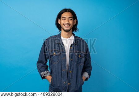 A Long-haired Asian Man In A Jean Shirt, Relaxes His Hand On His Jacket. A Young Man Stands Smiling
