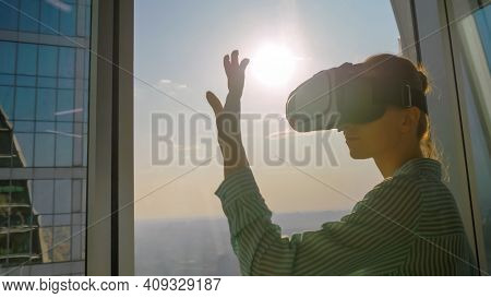 Woman Using Virtual Reality Headset And Moving Hand Against View On Cityscape From Panoramic Skyscra