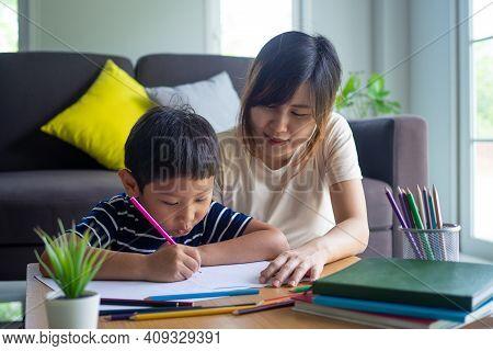 Mother Helping Son Writing Homework. Cute Asian Mother Helping Your Son Doing Your Homework .