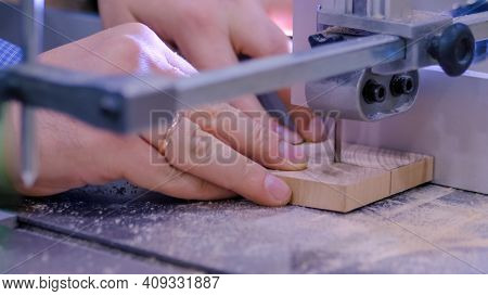 Professional Man Carpenter Hands Using Bandsaw Tool, Cutting Piece Of Wood At Workshop - Close Up. D