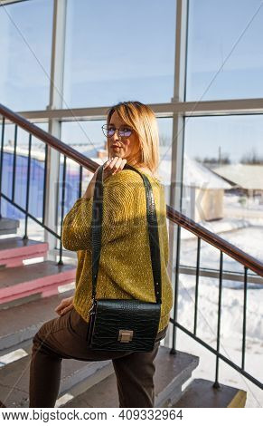 A Stylish Girl In A Yellow Sweater, Brown Trousers With A Small Womens Bag Poses Against The Backgro