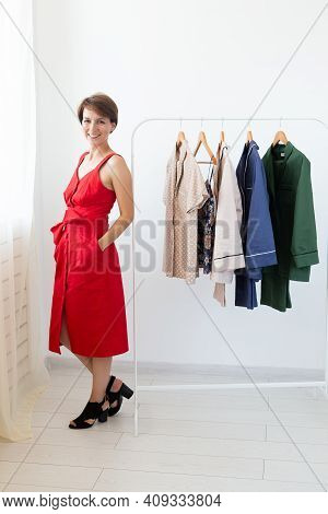 Female Stylist Near Rack With Hangers. Shopping, Clothes Designer And Consumerism Concept.
