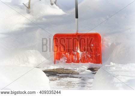 Snow Cleaning Concept. Red, Orange Shovel And Snow During Snowstorm. City Ervice Cleaning Snow Winte