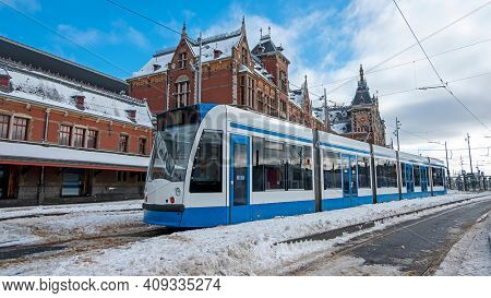 Tram waiting in winter in front of the Central Station in Amsterdam the Netherlands