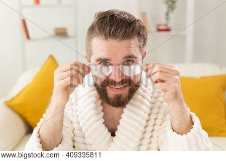 Bearded Man Removing Eye Patches On His Face. Wrinkles And Face Home Care For Men.