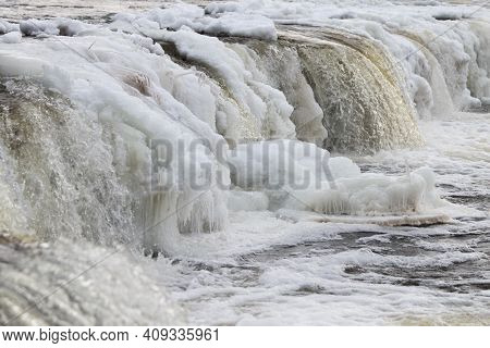 River Waterfall In Winter. Waterfall With Ice On A Cold Day