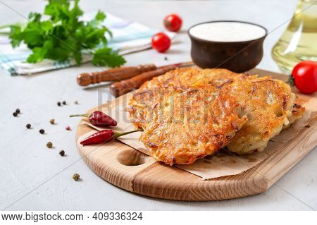 Potato Pancakes With Sour Cream On A Light Background. Vegetarian Dish.