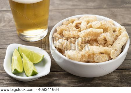 Fried Pork Cracklings On A White Bowl With Lemon And Beer Over Wooden Table.