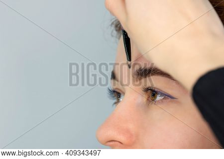 Young Caucasian Woman On The Brow Beauty Procedures. Professional Care For Face. Brows Coloring, Wax