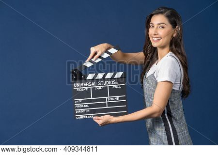 Happy Young Asian Woman Holding Movie Clapperboard On Studio Setup Film On Blue Color Background, Br