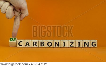 Carbonizing Or Decarbonizing Symbol. Businessman Turns Wooden Cube And Changes Words 'carbonizing' T