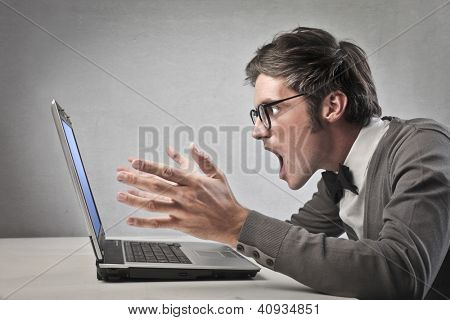 Fashionable man screaming against a laptop computer