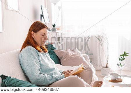 Reading A Book Concept. Caucasian Young Girl Wearing Casual Clothes Relaxing And Reading A Book On T