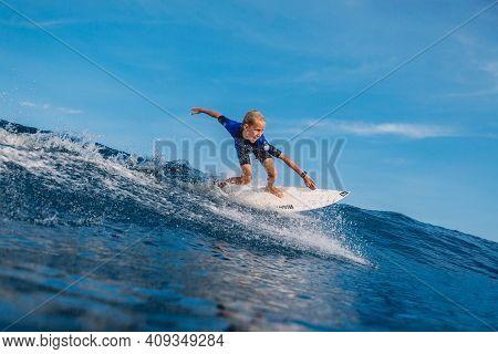 January 21, 2021. Bali, Indonesia. Caucasian Kid Surfer Ride At Ocean Wave On Surfboard.