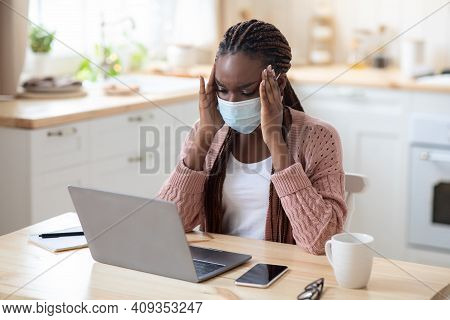 Stressed Black Woman In Medial Mask Suffering Problems While Working On Laptop In Kitchen, Concerned