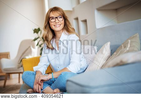 Attractive Woman Sitting On Couch At Home And Relaxing