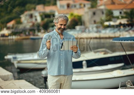 Portrait Of Retirement Handsome Senior Man Using Tablet Computer And Credit Card On Seafront